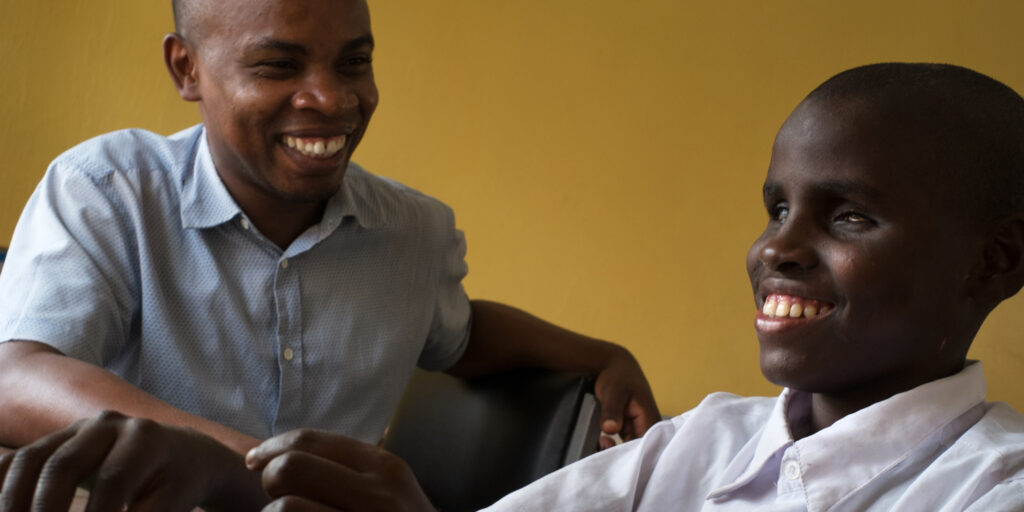 Schoolboy with deafblindness and his friend laughing
